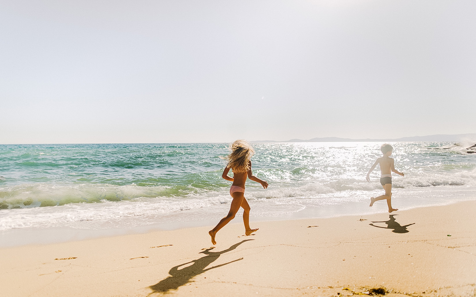 two children running along the beach