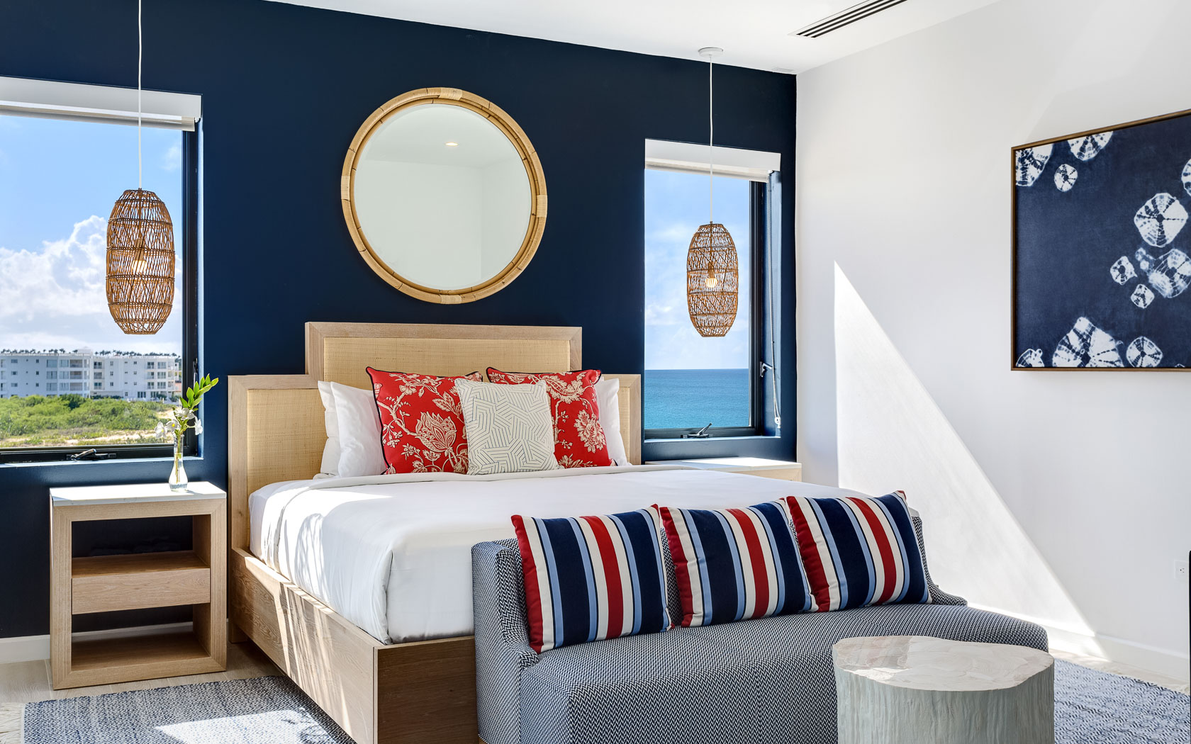 large bed in center of room with two windows and navy blue accent wall