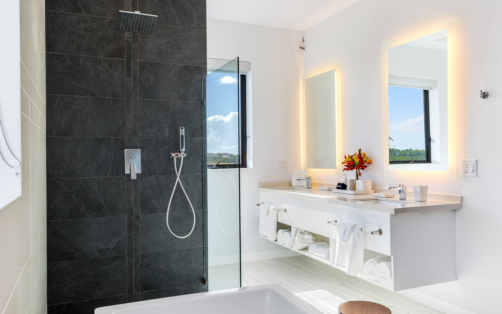 luxurious bathroom with double sinks and black stone shower