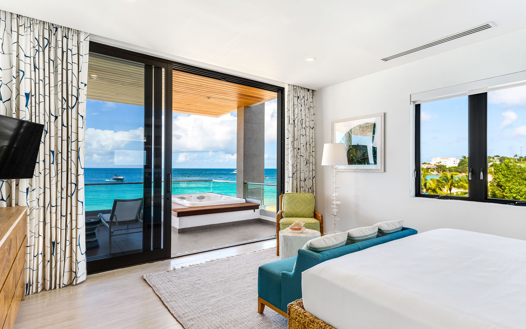 bedroom with bed facing glass doors and views of ocean