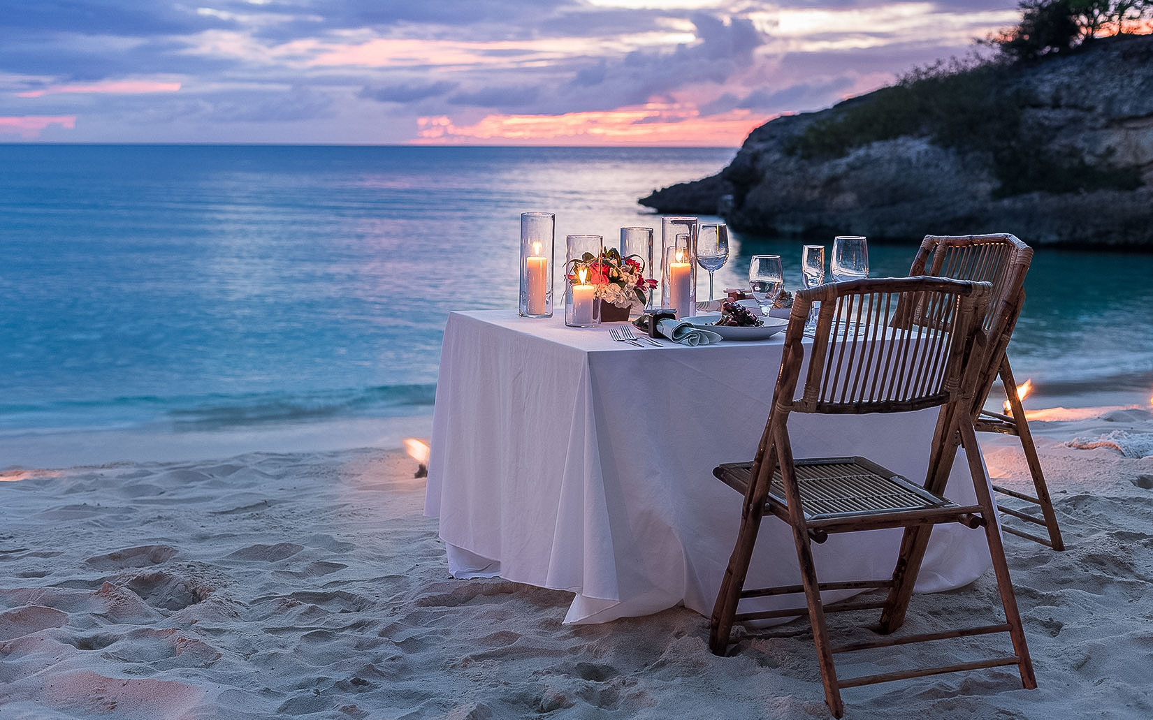 small table with candles and table settings for two on beach at sunset