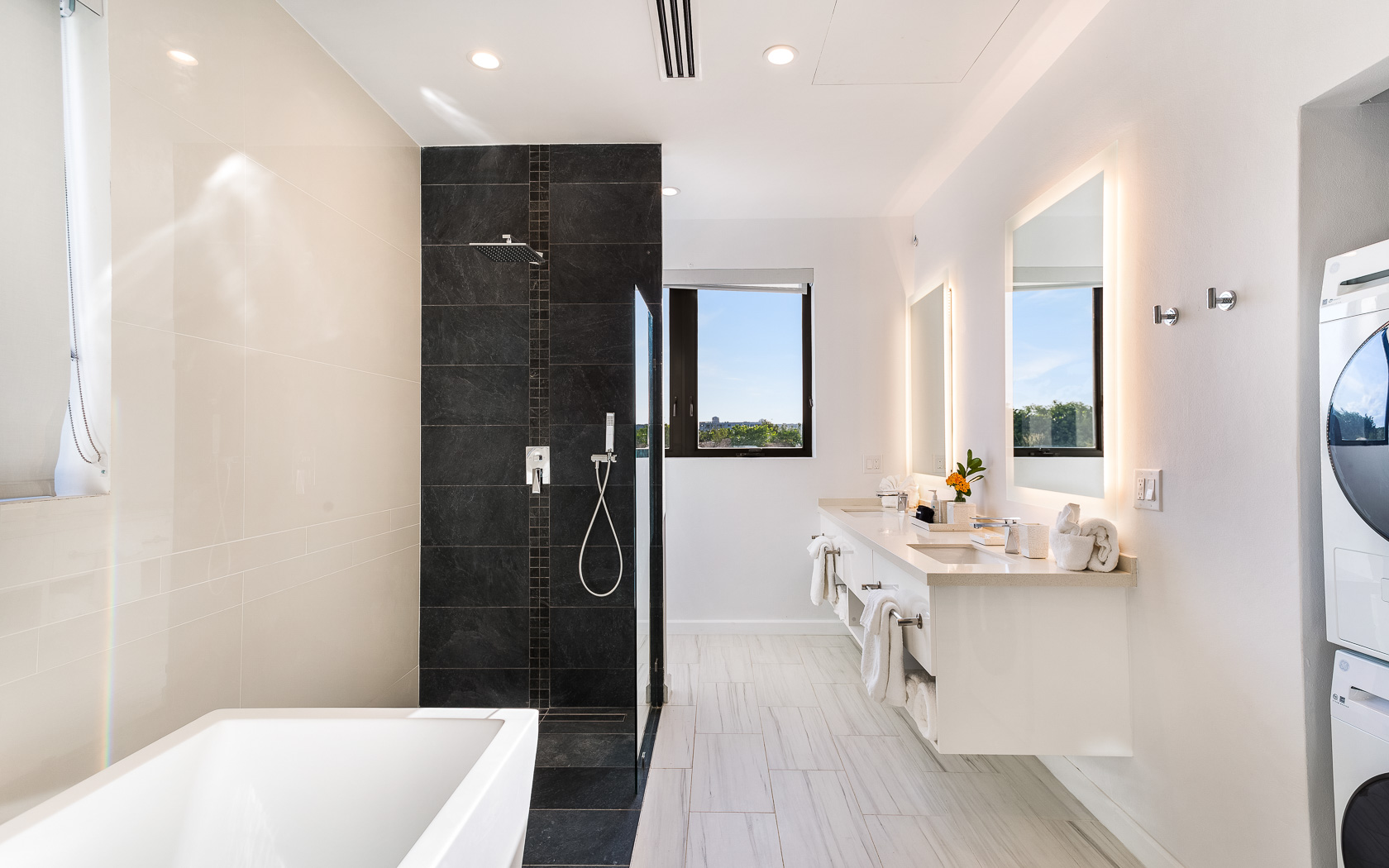 white bathroom with double sinks and black accent shower