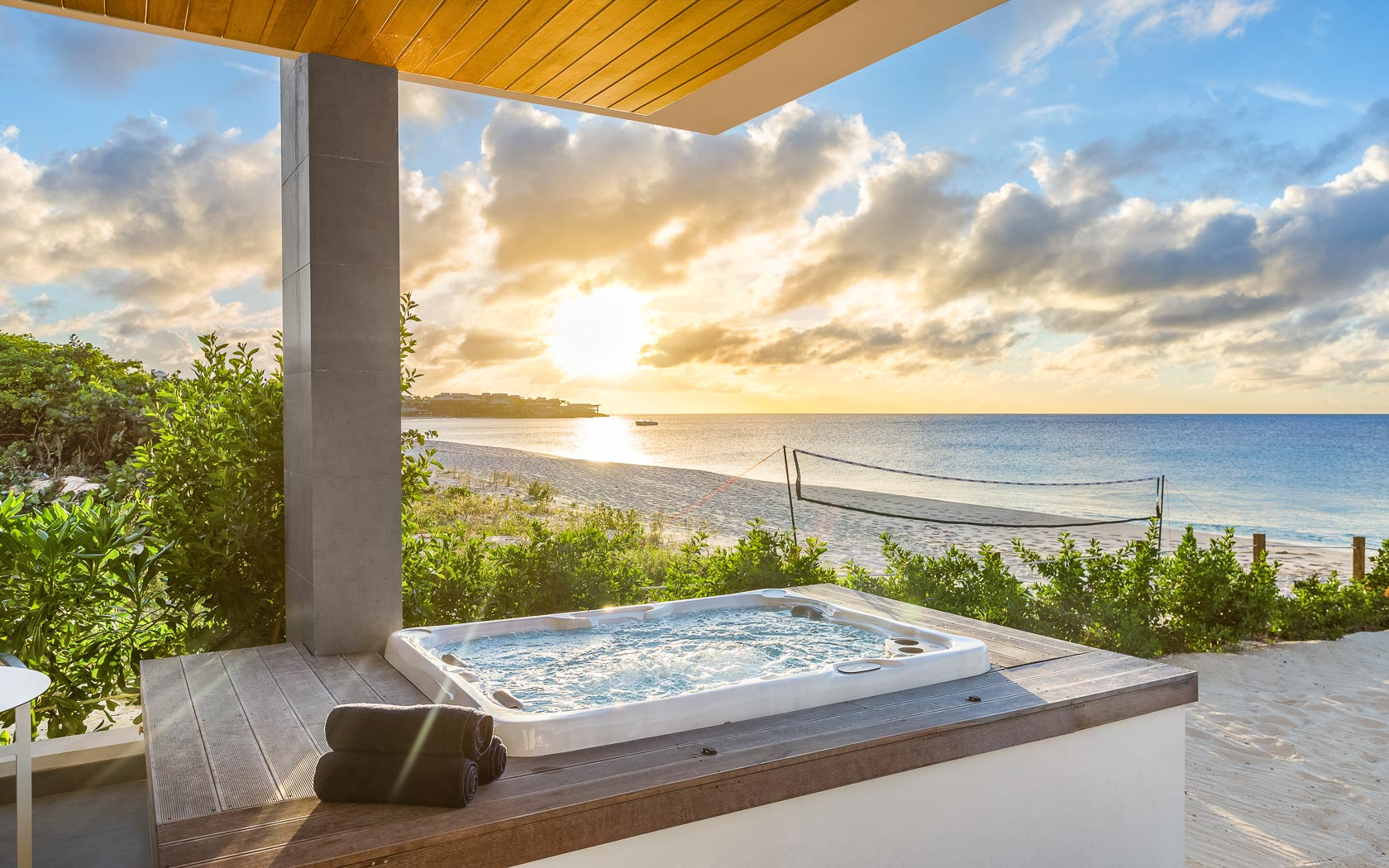 shot of hot tub while sun rises over ocean
