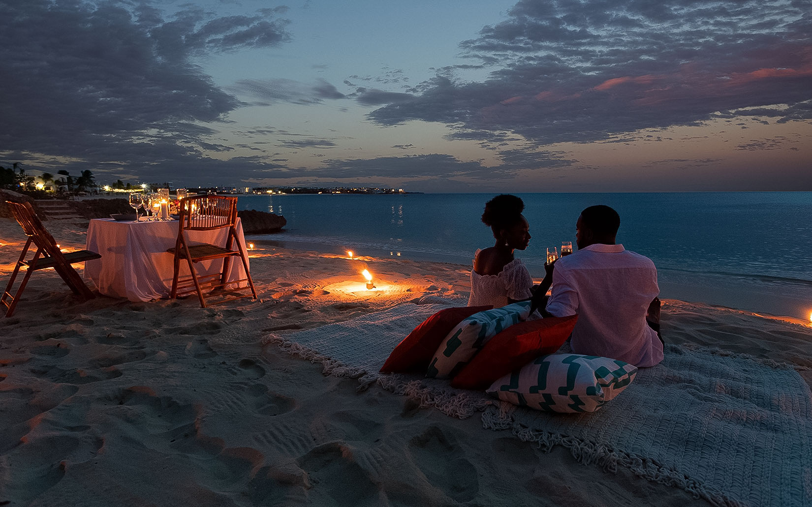 couple on nighttime beach date with warm lights in sand