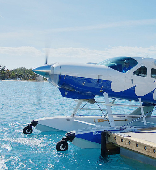 Sea plane sitting on water next to dock