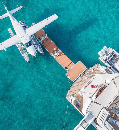 A sea plane and a smaller boat are docked on a yacht platform