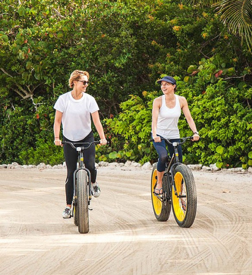 Two friends riding bikes in the sand