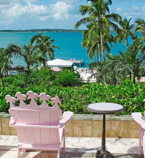 Two pink outdoor chairs facing the ocean