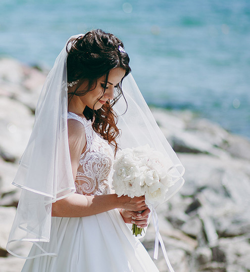 A bride holding bouquet of flowers standing on rocky ocean shore