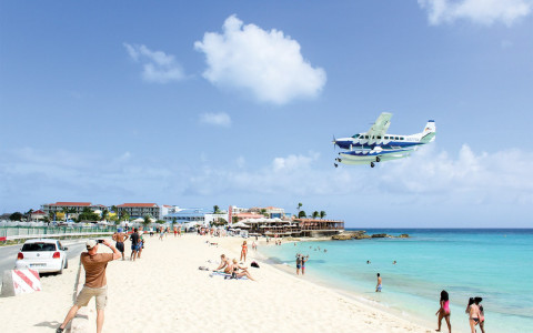 A sea plane flies over a beach as all the beach goers look up at it