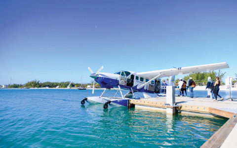Sea plane sitting on water next to dock with people about to board