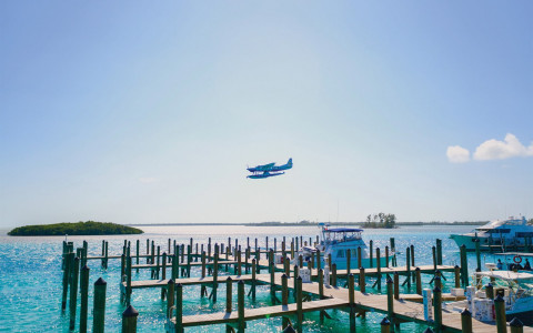 A sea plane flies over an empty dock as ocean glistens under the sun