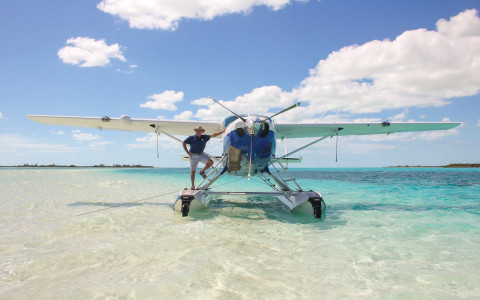 A man poses next to a parked sea plane on a beach