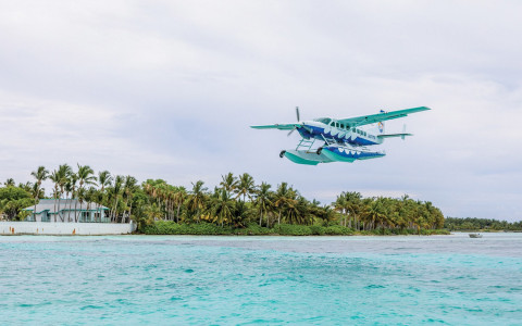 A sea plane flying just over the ocean near an island