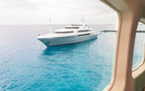 A large yacht as seen outside the window of a sea plane