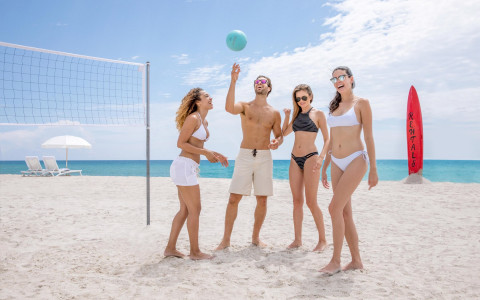 group of friends about to play beach vollyball