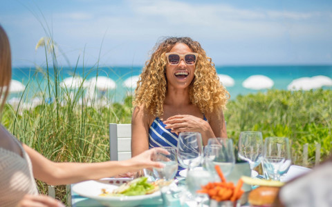 woman sitting and laughing at table set up for a meal with the beach in the background