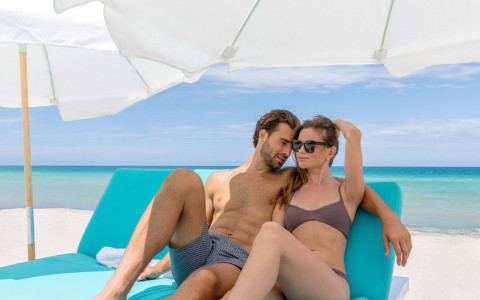 couple with swimsuits laying on a blue lounge chair with white umbrella on the beach