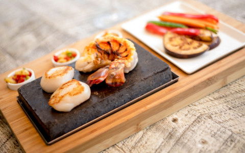 wooden tray with seafood such as shrimp and scallops placed on a stone platter on the tray