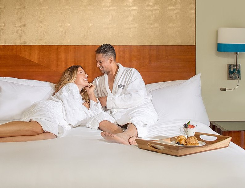 man and woman sitting on a bed with their bath robes