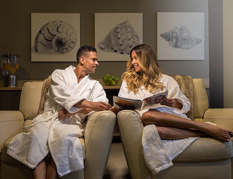 man and woman sitting in Aquanox lobby in their spa robes
