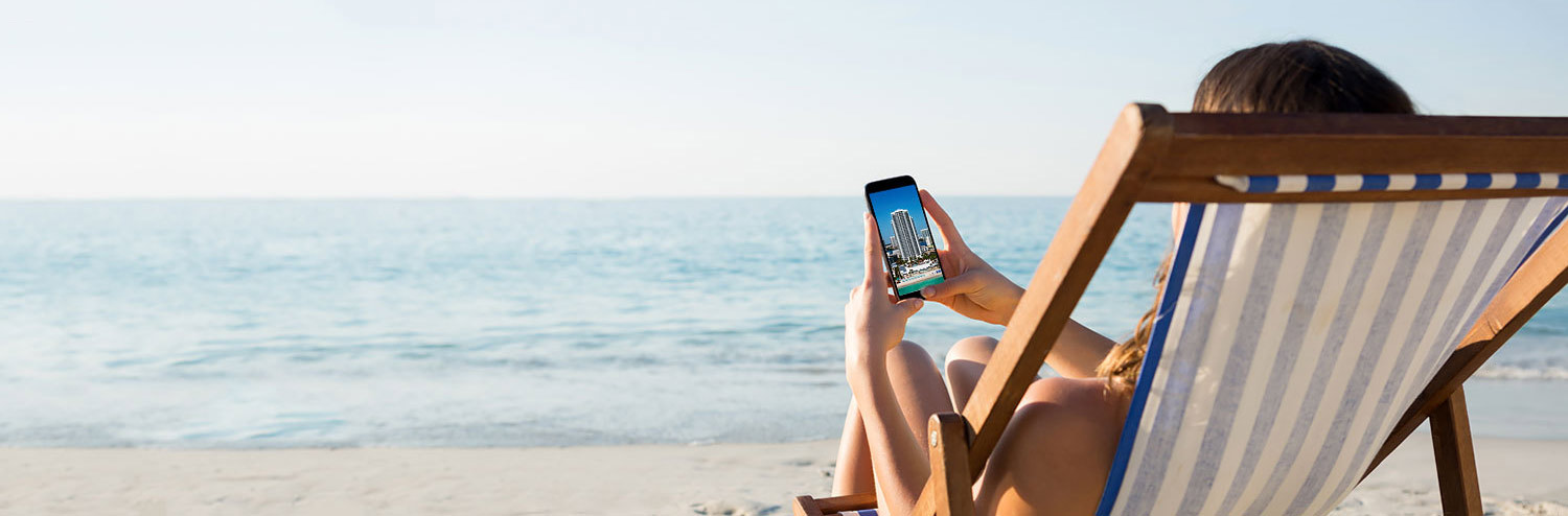 woman sitting at the beach looking at her phone