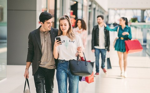 man and woman walking inside a mall looking at their phone