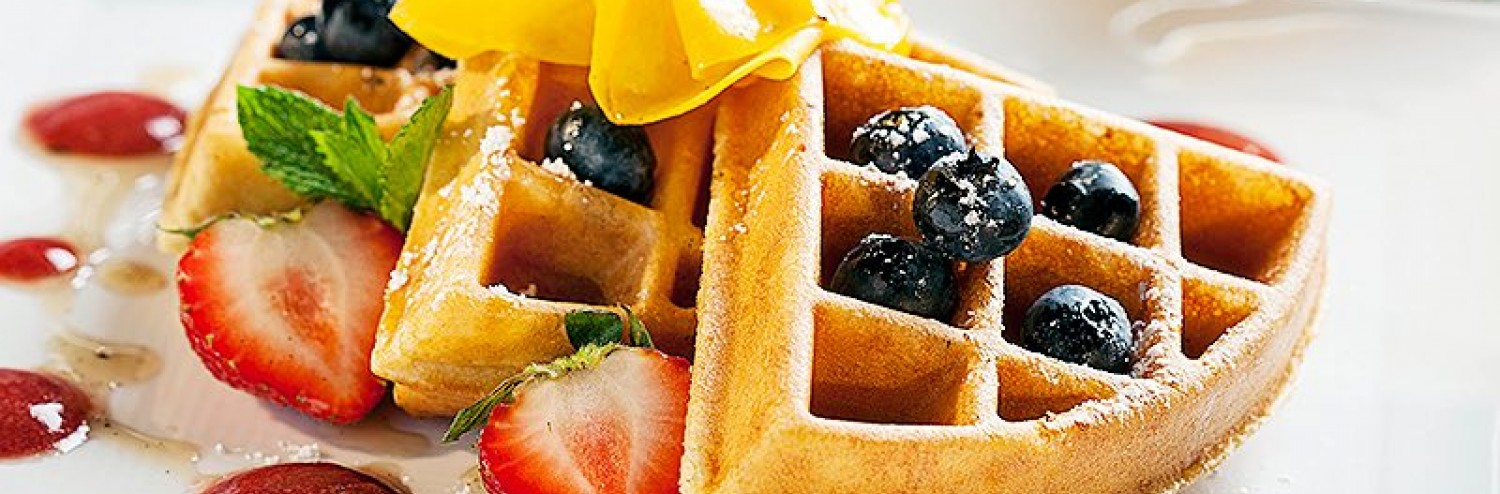 three waffle pieces garnished with fruit