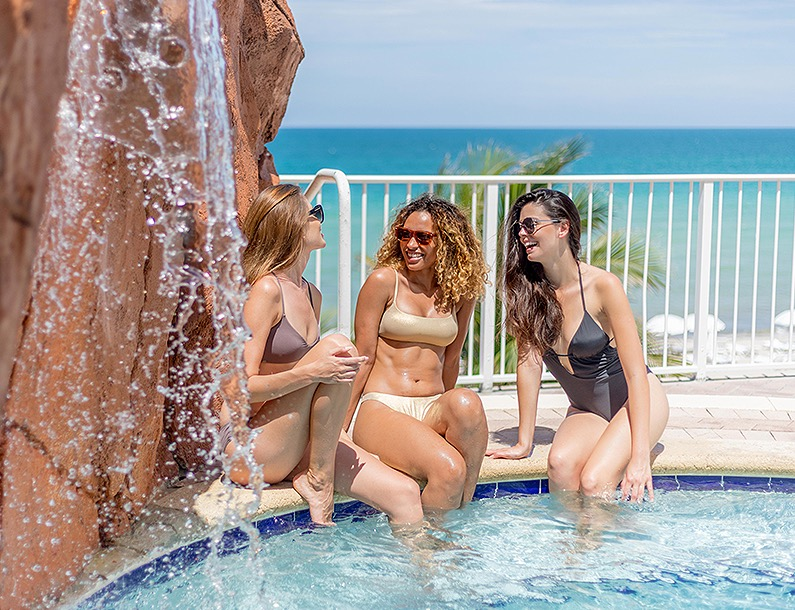 three girlfriends by the waterfall pool
