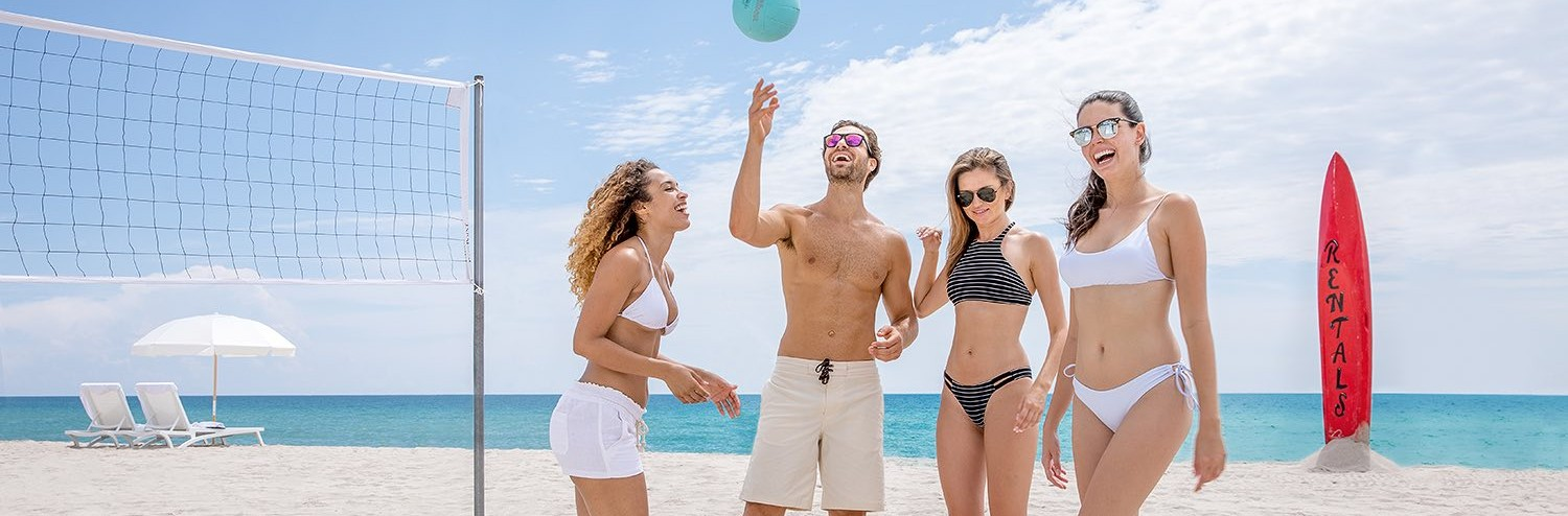 four friends playing beach volleyball