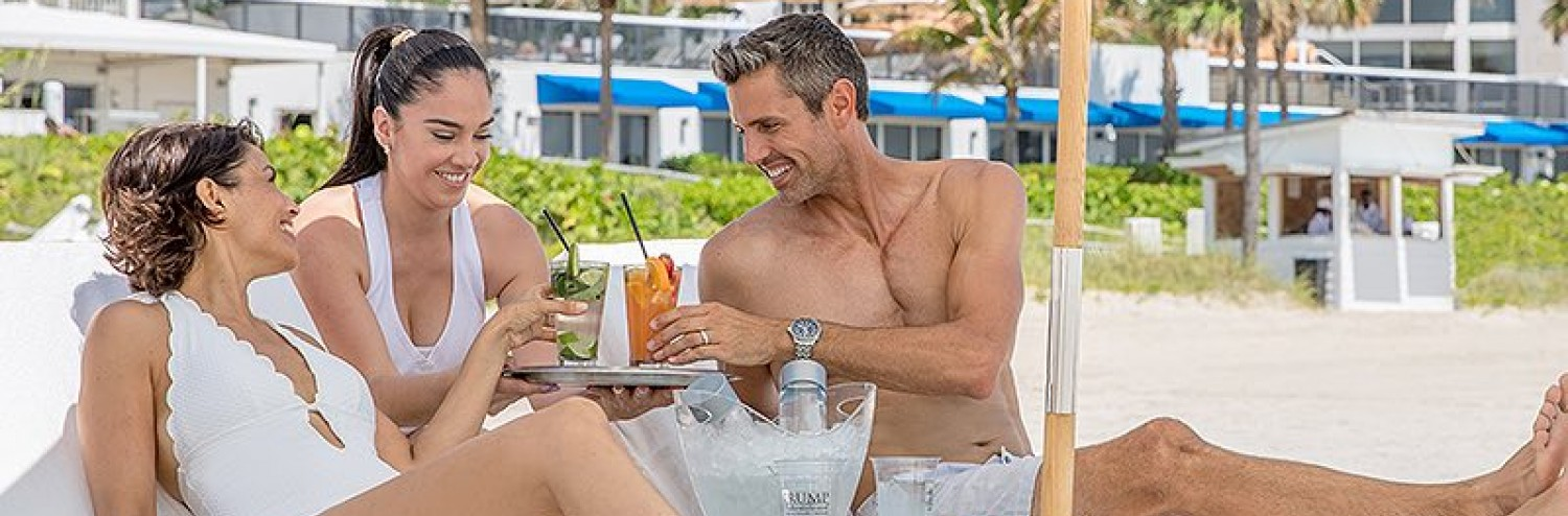 man and woman being served drinks beachside