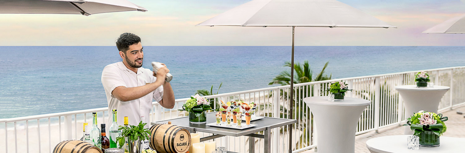 bartender making drinks poolside at trump international beach resort