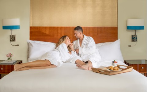 man and woman sitting on a bed in their robes
