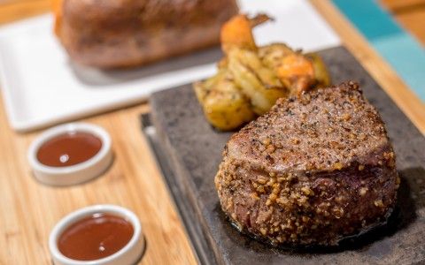 steak being served on a plank with baked potato