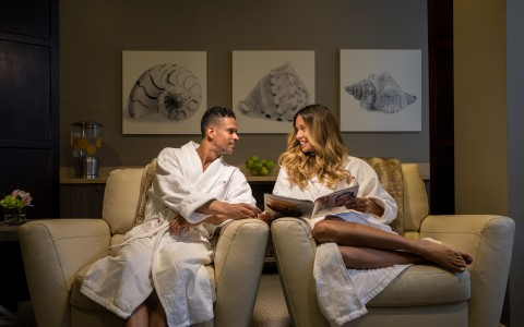 man and woman sitting at the spa lobby wearing robes