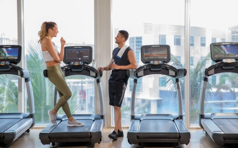 man and woman chatting at the trump international beach resort fitness center