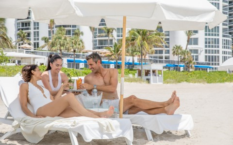 man and woman bring served drinks on the beach by waitress