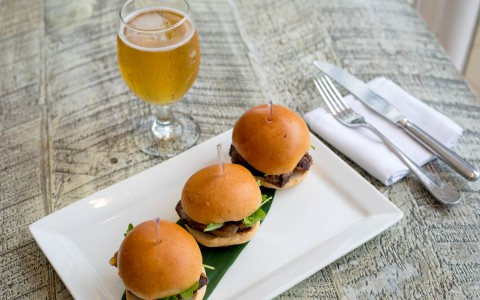 three sliders with a glass of beer