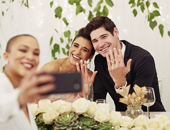 wedding guest taking a selfie with bride and groom