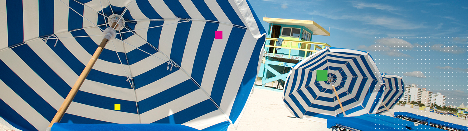 Blue & white striped umbrellas on sand with lifeguard shed in the back