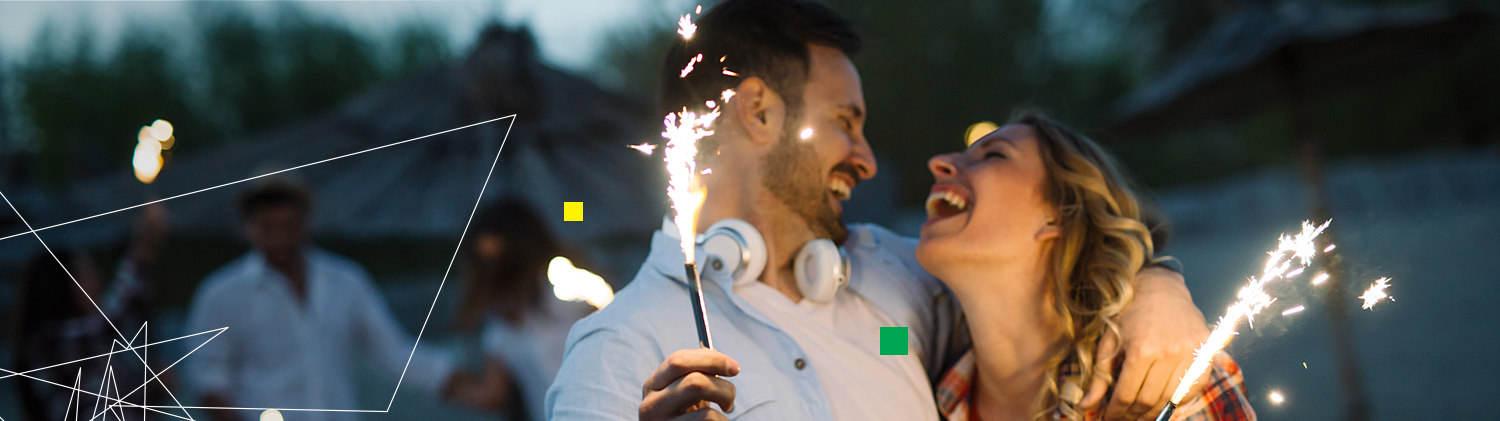 Couple laughing with sparklers in hand