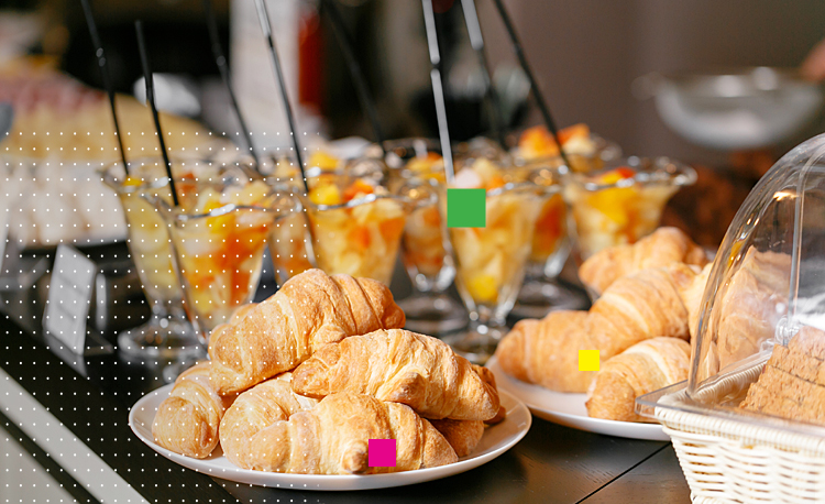 Plates of croissants next to glass fruit cups