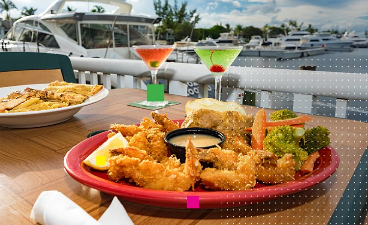 Table with breaded shrimp on plate & cocktails next to marina with yachts