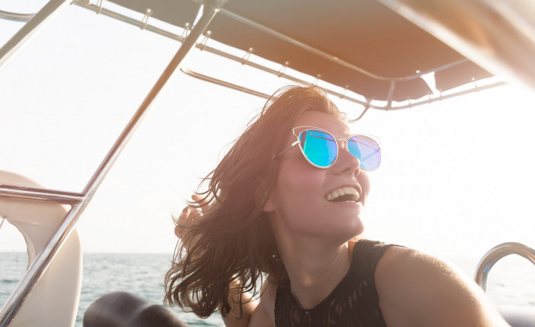 Woman with blue sunglasses in riding in yacht