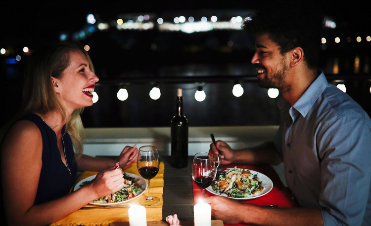 Couple having dinner with wine next to the water