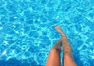 legs in the blue pool red toe nails