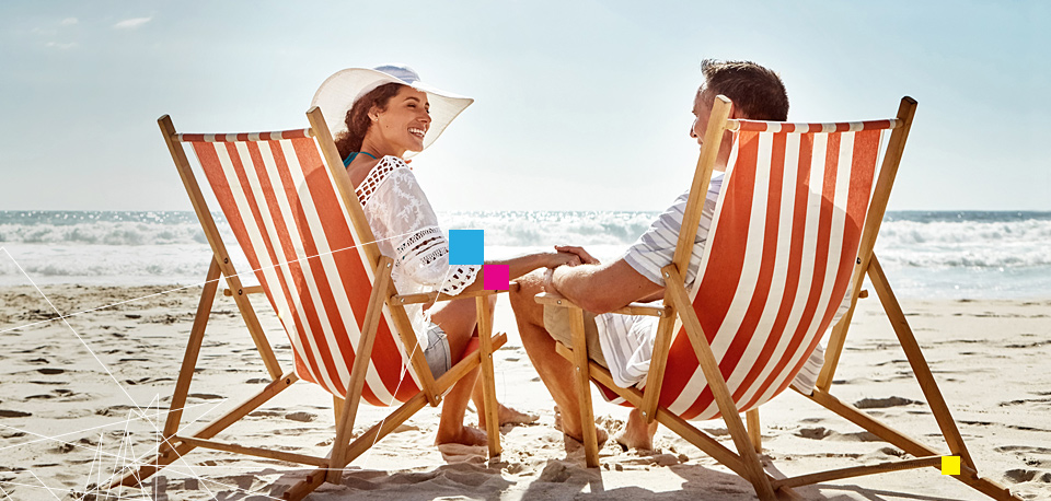 Couple sitting on lounge chairs at the beach
