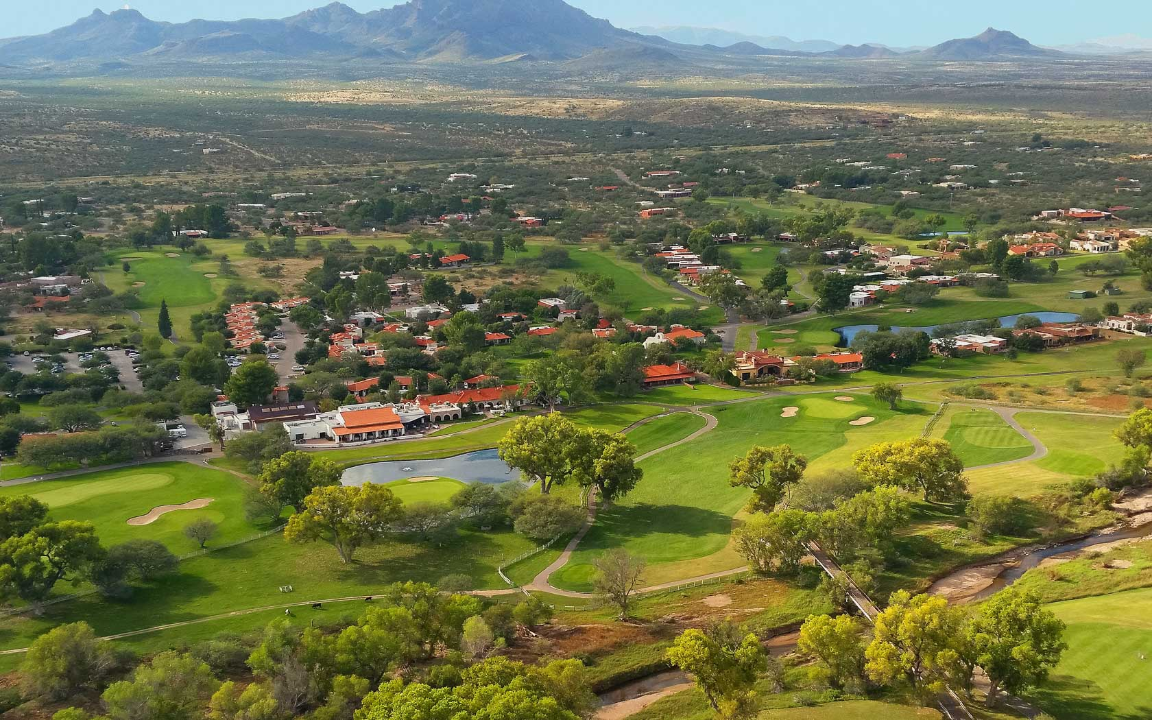 aerial view of the property including the golf course and the mountains in the distance