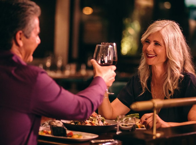 couple clinking their wine glasses over a nice dinner