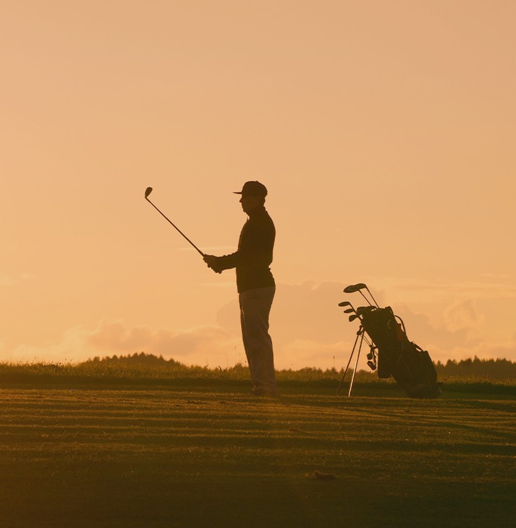 golfer standing outside with golf club up in the air